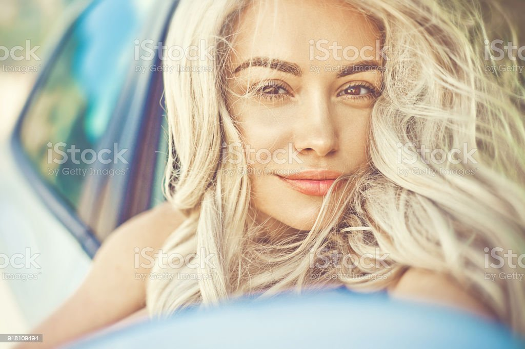 Beautiful young blonde in car on the beach stock photo