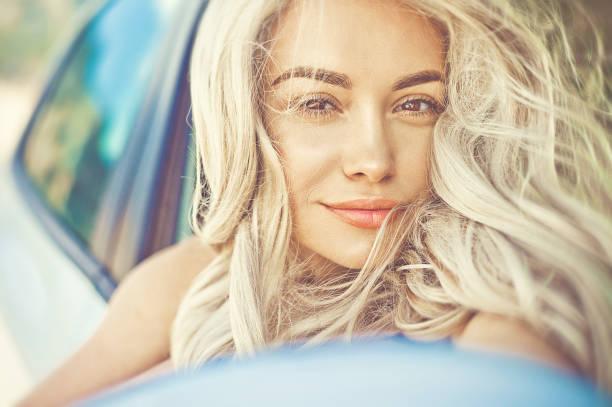 schöne junge blondine im auto auf dem strand - soup_studio stock-fotos und bilder