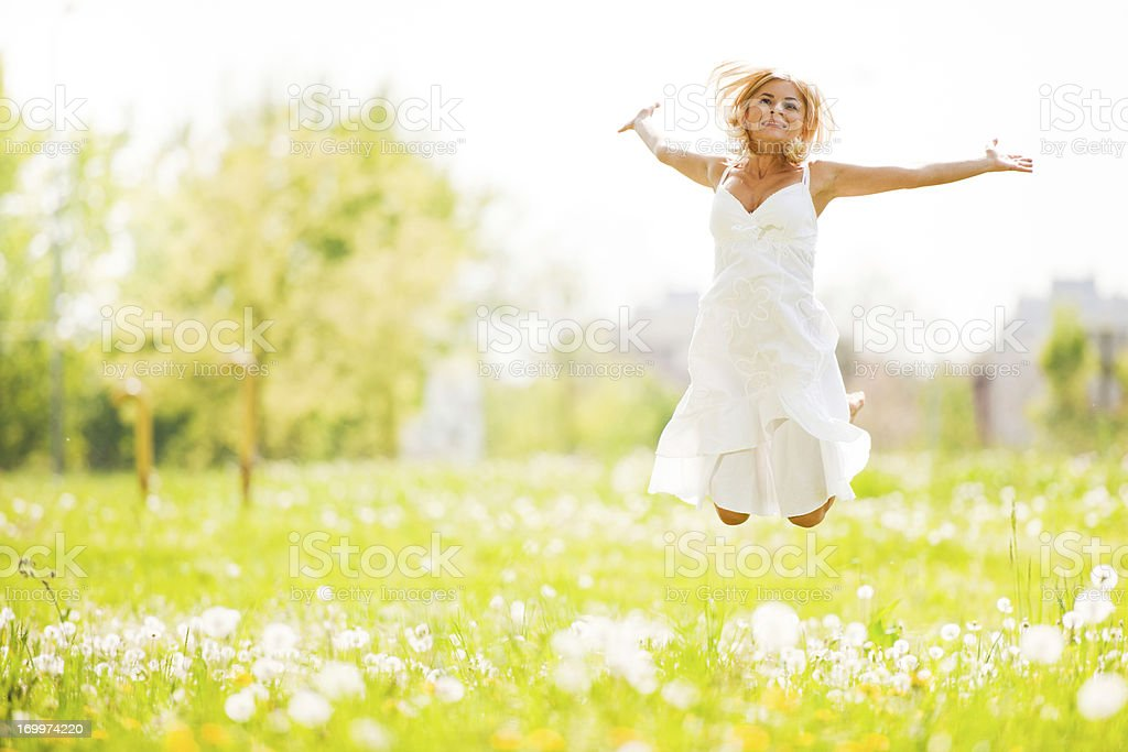 Beautiful young blonde jumping in the park royalty-free stock photo