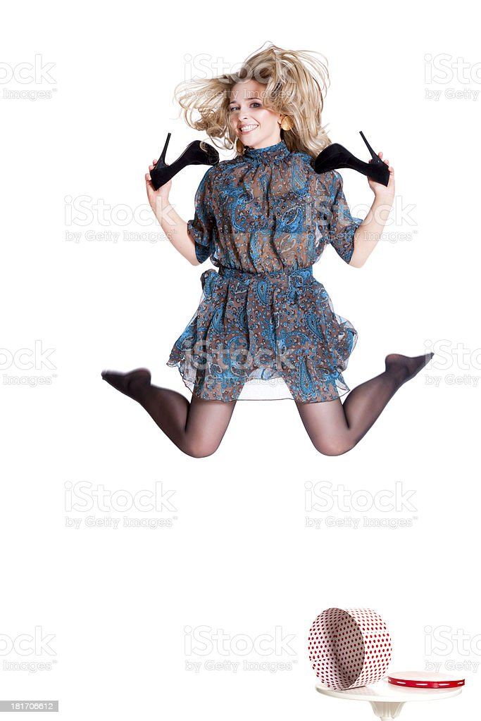 Beautiful young blonde jumping with shoes in hand royalty-free stock photo