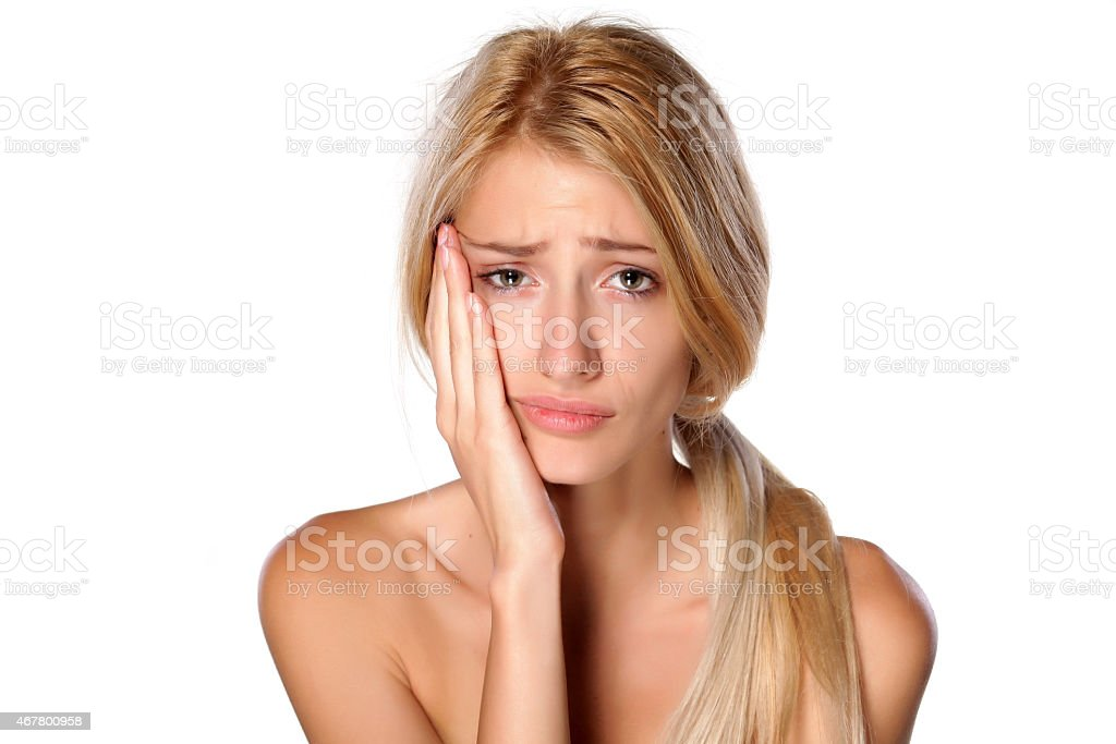 Beautiful young blonde with a toothache on white background stock photo