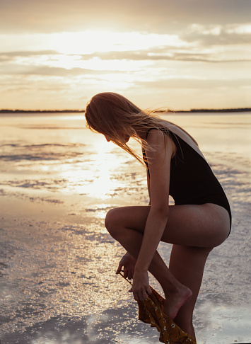 Beautiful young blonde with long hair dresses up on the lake shore. Walk during sunset. Girl in a bathing suit