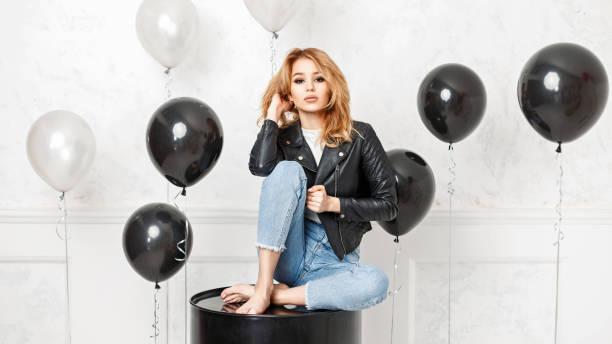 schöne junge blonde frau in einem schwarzen jacke sitzt auf einem schwarzen metallschaft - ballonhose stock-fotos und bilder
