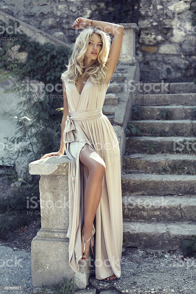 Beautiful young blonde woman in beige dress posing by stairs stock photo
