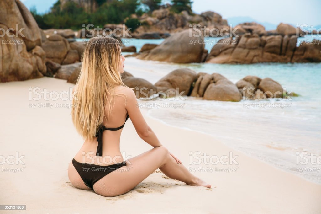 Beautiful Young Blonde Woman In Black Bikini Posing On The Beach In Turning Booty Shows Ass