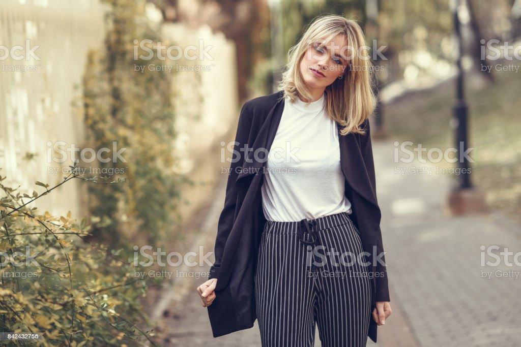 Hermosa joven rubia en fondo urbano - foto de stock