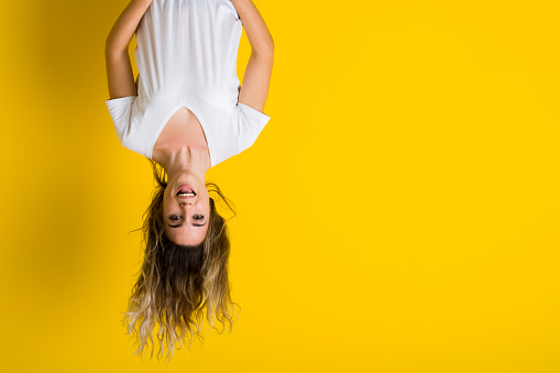 istock Beautiful young blonde woman jumping happy and excited hanging upside down over isolated yellow background 1079842648