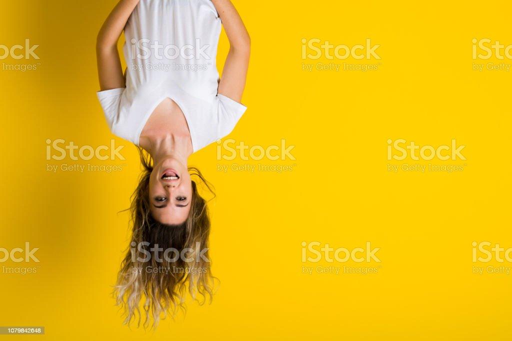 Hermosa joven rubia saltando feliz y emocionado que cuelga boca abajo sobre fondo amarillo aislado - foto de stock