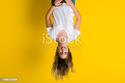istock Beautiful young blonde woman jumping happy and excited hanging upside down over isolated yellow background 1098300958