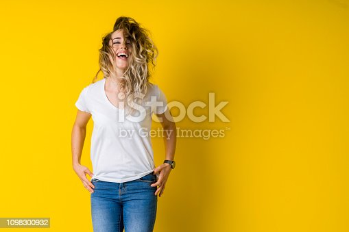 istock Beautiful young blonde woman jumping happy and excited over isolated yellow background 1098300932