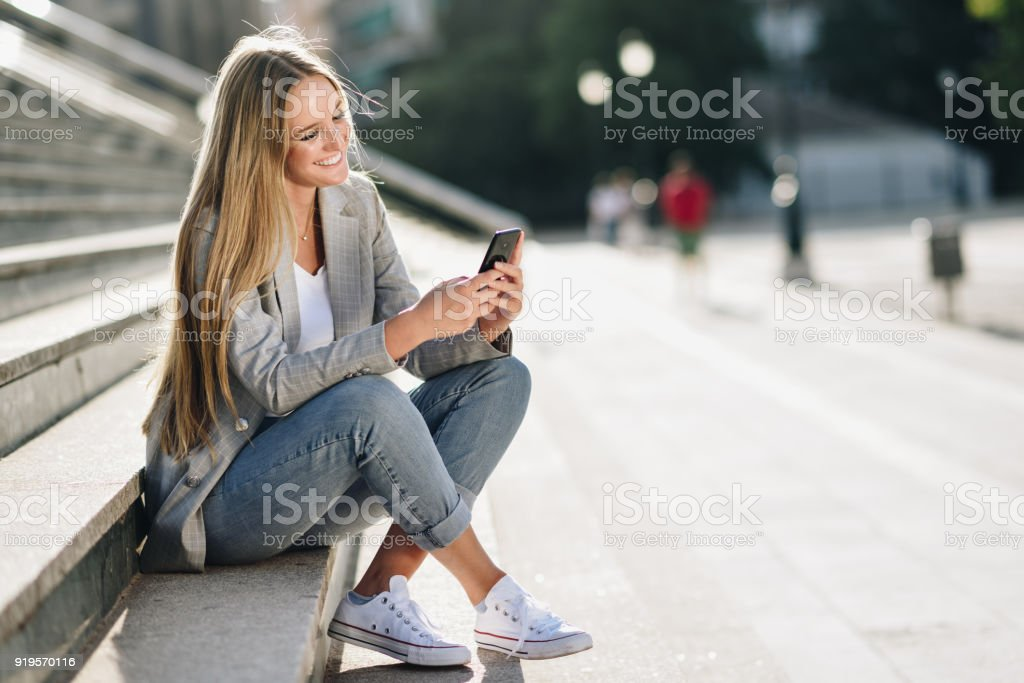 Beautiful young blonde woman looking at her smartphone and smiling. stock photo