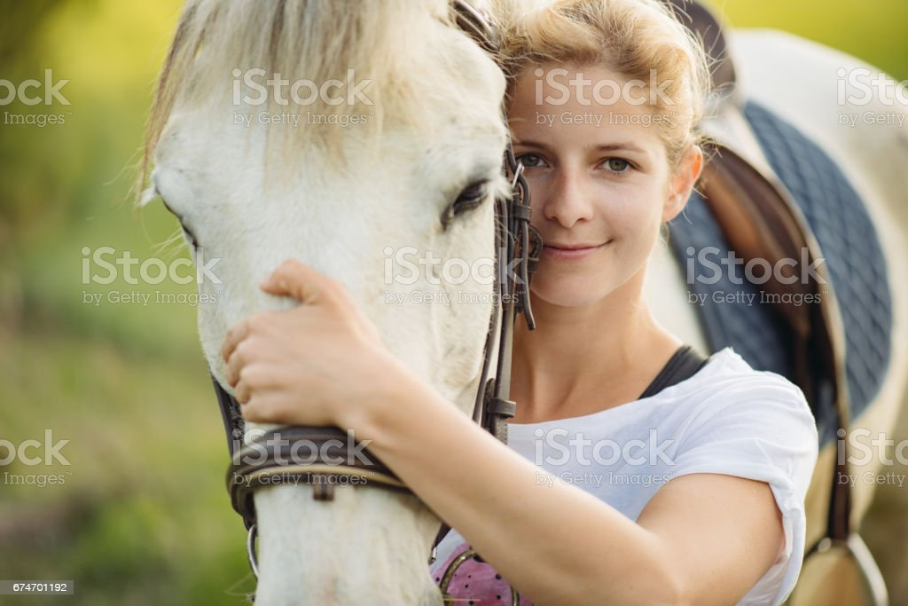 Beautiful young blonde woman portrait with her horse stock photo