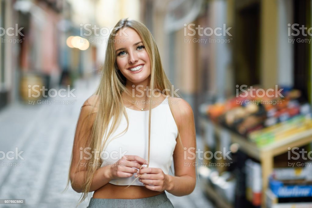 Beautiful young blonde woman smiling in urban background. stock photo