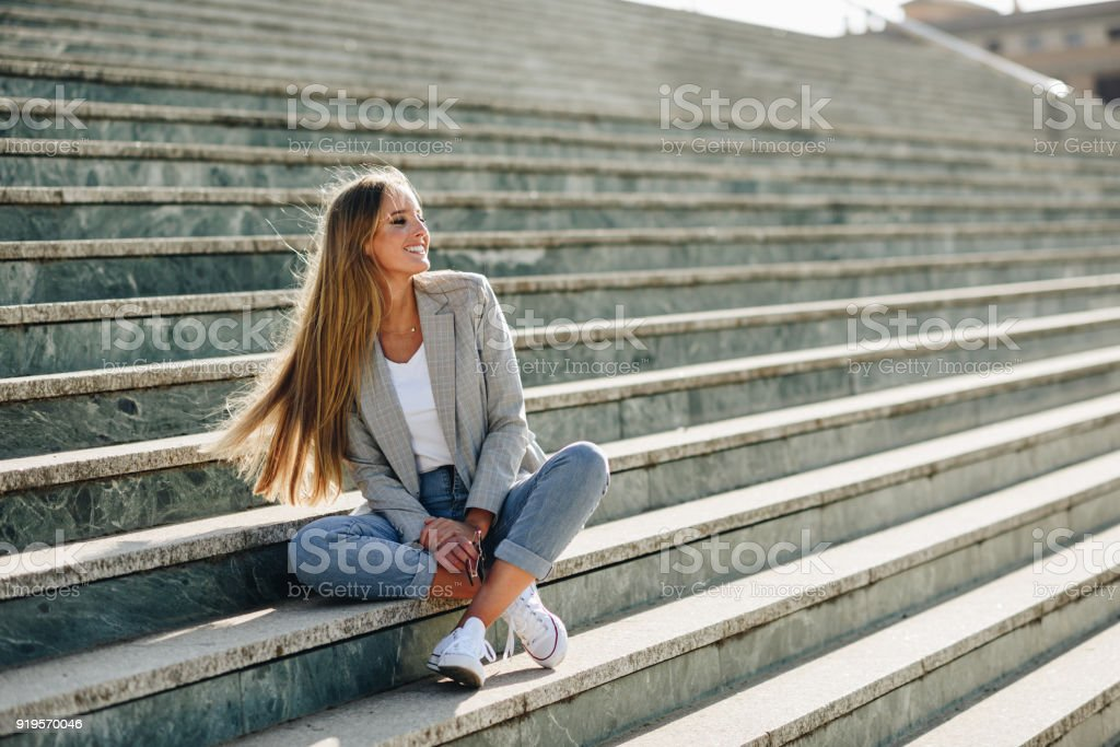 Beautiful young blonde woman smiling on urban steps. stock photo
