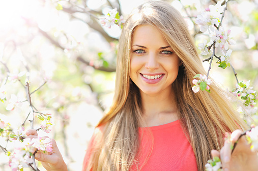 Beautiful young blonde woman standing near blooming tree