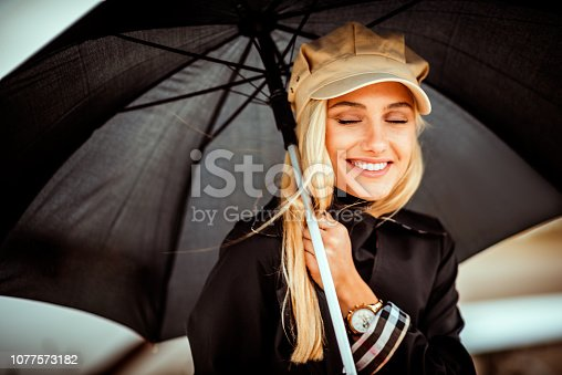 Beautiful young blonde woman standing in front of a private airplane parked on an airport runway tarmac. She is holding a big black umbrella.