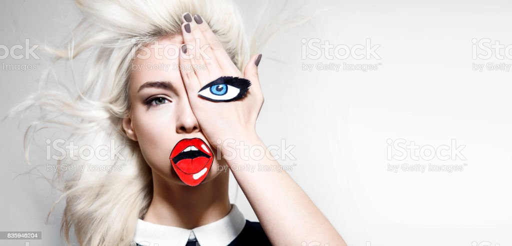 Beautiful young blonde woman with blue eyes with lush eyelashes and red lips painted on paper stock photo
