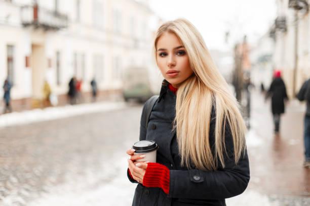 schöne junge blonde frau mit kaffee in einen mode-wintermantel in der stadt - wintermantel damen wolle stock-fotos und bilder