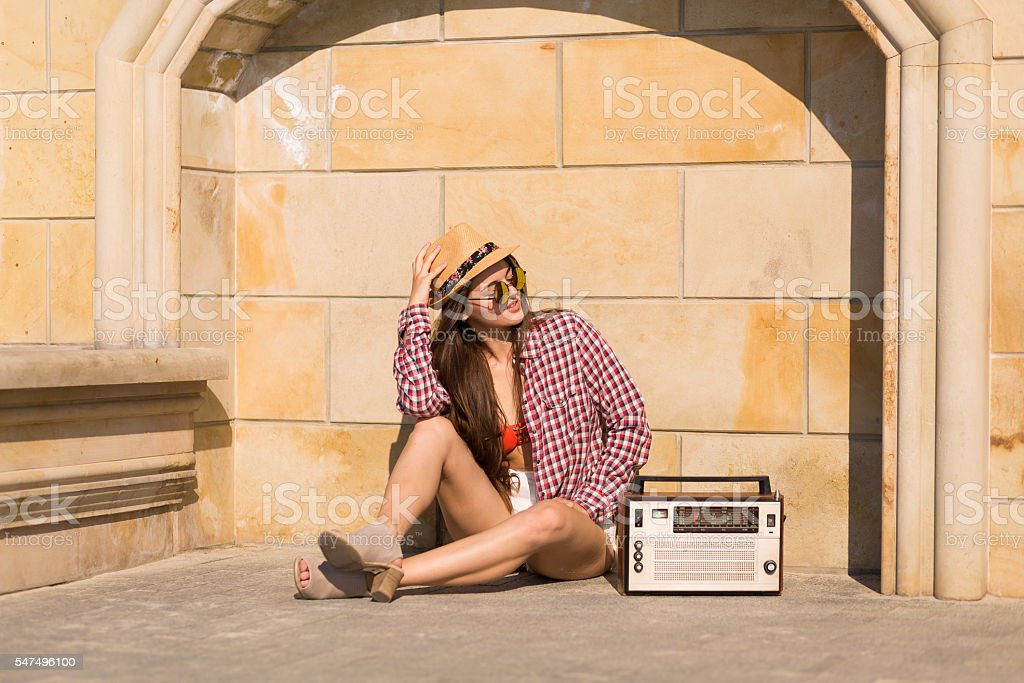Beautiful young boho woman with a retro stereo stock photo