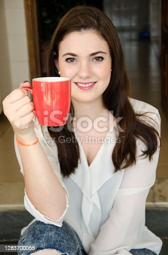 Young woman having some coffee in a vibrant red cup, and looking straight at the camera.