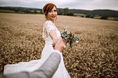 Chic Boho Styled Bride With Lovely  Big Bouquet Holding Hands of Her Husband Happily Heading To Wheat Field