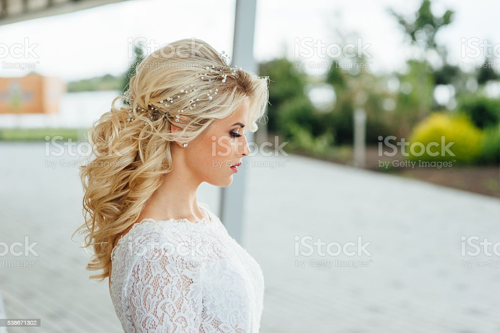 Beautiful young bride in luxury wedding dress stock photo