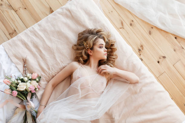 Beautiful young bride in sexy lingerie lies on a bed with a bouquet of flowers. Top horizontal view stock photo