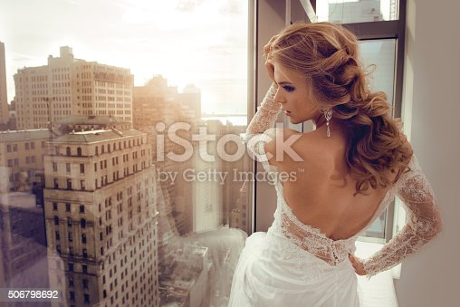 506798692 istock photo Beautiful Young bride in wedding dress posing near window 506798692