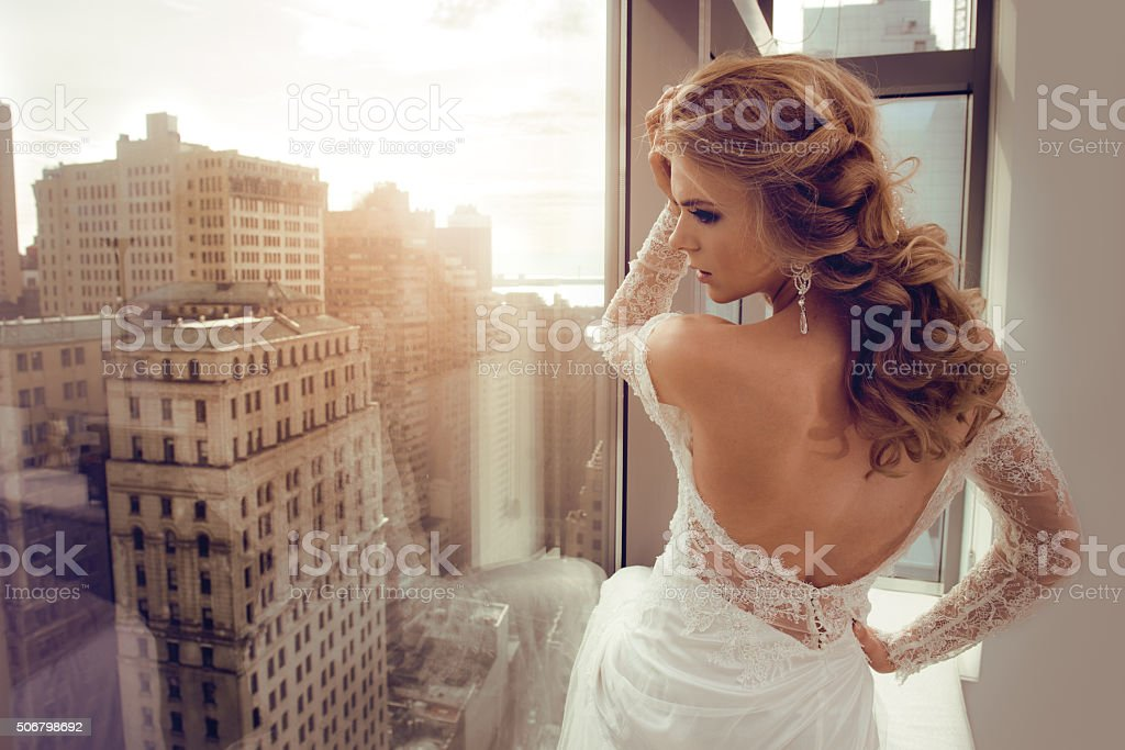 Beautiful Young bride in wedding dress posing near window stock photo