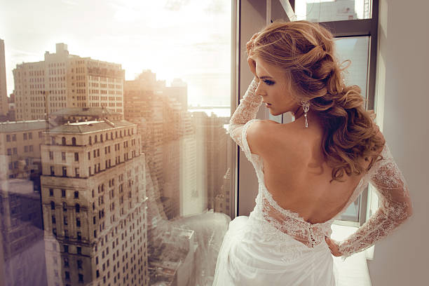beautiful young bride in wedding dress posing near window - wedding fashion stock photos and pictures
