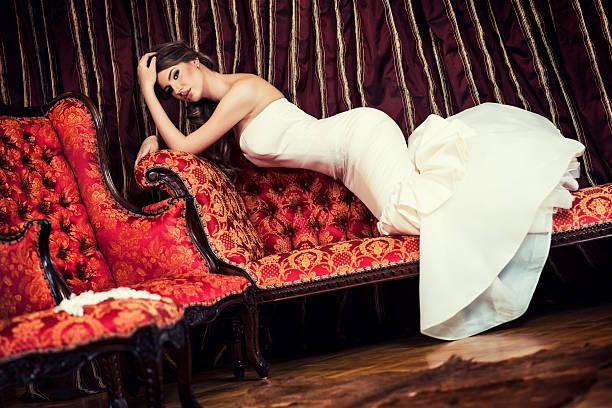 schöne junge braut auf dem sofa liegende innerhalb des barock-innengestaltung - hochzeits make up blaue augen stock-fotos und bilder