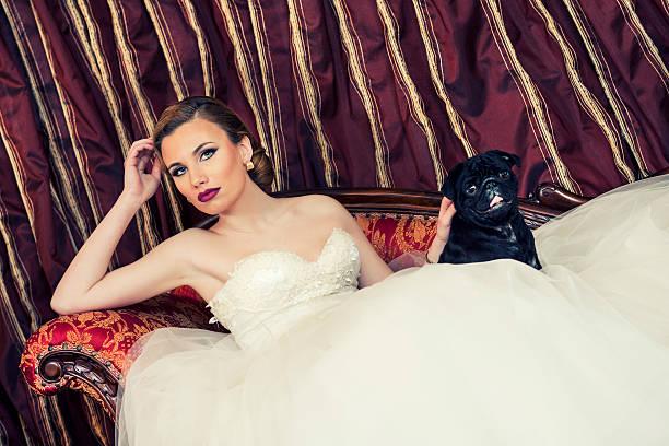 schöne junge braut liegen auf der couch mit ihrem hund-hund - hochzeits make up blaue augen stock-fotos und bilder