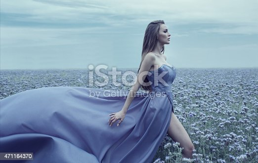 Beautiful young bride walking on the field of flowers