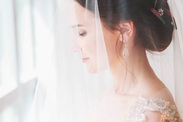 beautiful young bride with wedding makeup and hairstyle in bedroom. beautiful bride portrait with veil over her face. close-up portrait of young gorgeous bride. - veil stock pictures, royalty-free photos & images