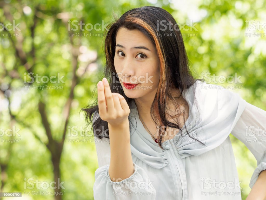 Beautiful young brunette Asian woman doing a rich gesture or counting money concept. Outdoor fashion portrait of glamour young Chinese stylish lady. Emotions, people, beauty and lifestyle concept. stock photo