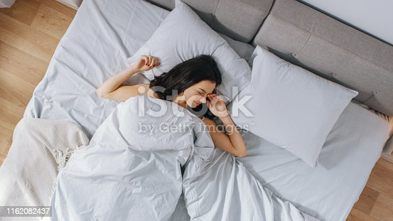 istock Beautiful Young Brunette Charmingly Sleeps in Her Bed in the Early Hours of the Morning. Sweet and Warm View of Girl Sleeping Calmly. Top Down Camera Shot. 1162082437