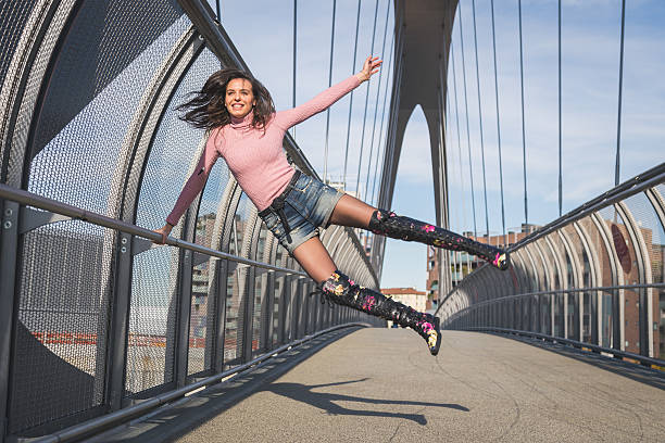 Bela jovem pulando em uma ponte brunette - foto de acervo