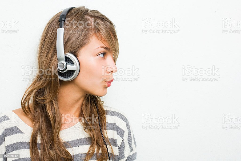 Beautiful young brunette listening to music in silver headphones. stock photo