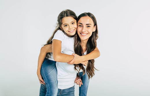 istock Beautiful young brunette mother holds on back her cute little daughter in white T-shirts isolated in studio 1132216702