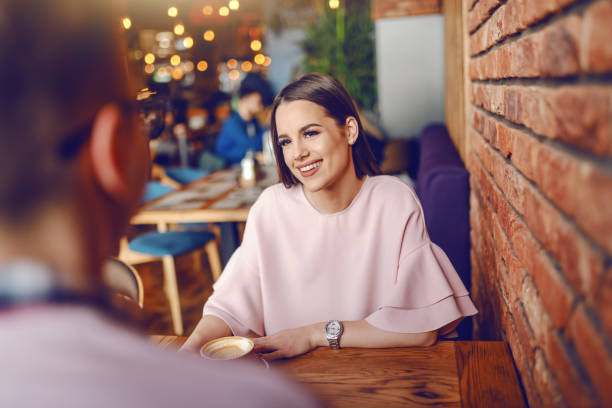 Beautiful young brunette sitting in cafeteria, drinking coffee and flirting with her boyfriend. Beautiful young brunette sitting in cafeteria, drinking coffee and flirting with her boyfriend. date stock pictures, royalty-free photos & images