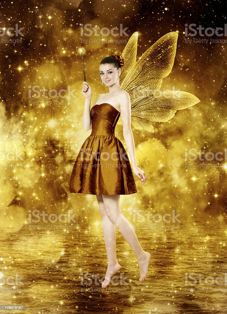 Beautiful young brunette woman as golden fairy stock photo