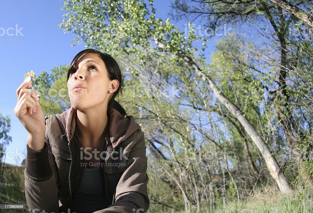 Beautiful young brunette woman eating food in the woods  stock photo