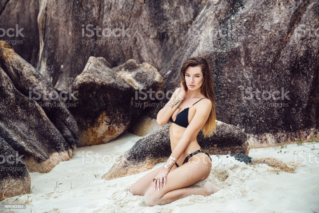 0fdde10ec Beautiful young brunette woman in black bikini posing on the beach. Sexy  model portrait with perfect body. Concept of summer holidays - Stock image .