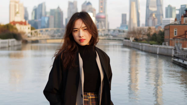 Beautiful young brunette woman in black clothes smiling at camera with  blur Shanghai Bund landmark buildings background in autumn dusk light. Emotions, people, beauty, travel and lifestyle concept. stock photo