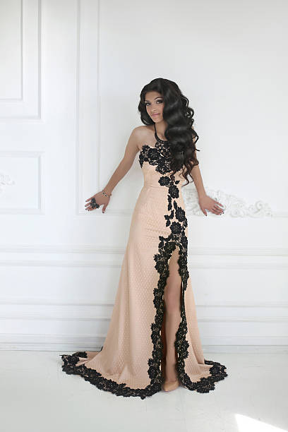 beautiful young brunette woman in elegant dress with long hair - prom fashion stock photos and pictures