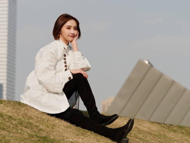 schöne junge brünette frau im weißen hemd sitzend und lächelnd in der kamera mit der hand auf ihrem gesicht an sonnigen tag. outdoor-mode-porträt von glamour chinesischen fröhliche stilvolle mädchen. - damen hosen angels stock-fotos und bilder