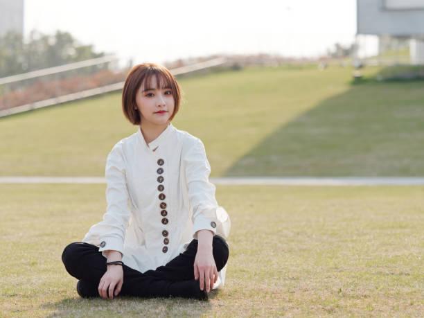 schöne junge brünette frau im weißen hemd sitzt auf wiesen mit bein gekreuzt und lächelnd in der kamera an sonnigen tag. outdoor-mode-porträt von glamour chinesischen fröhliche stilvolle mädchen. - damen hosen angels stock-fotos und bilder