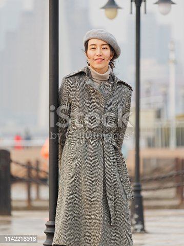 Beautiful young brunette woman looking and smiling with blur street background. Outdoor fashion portrait of glamour Chinese cheerful stylish lady. Emotions, people, beauty and lifestyle concept