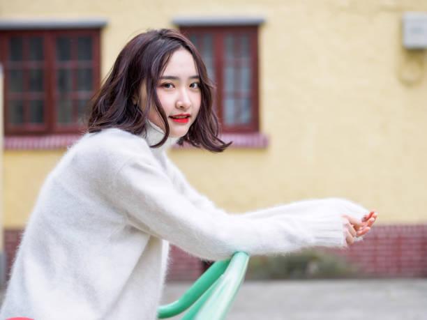 カメラを見て美しい若いブルネットの女性は、家の背景をぼかし。グラマーの若い中国陽気のスタイリッシュなの女性、感情、人々、美容、ライフ スタイル コンセプトのアウトドアファッションの肖像画。 ストックフォト