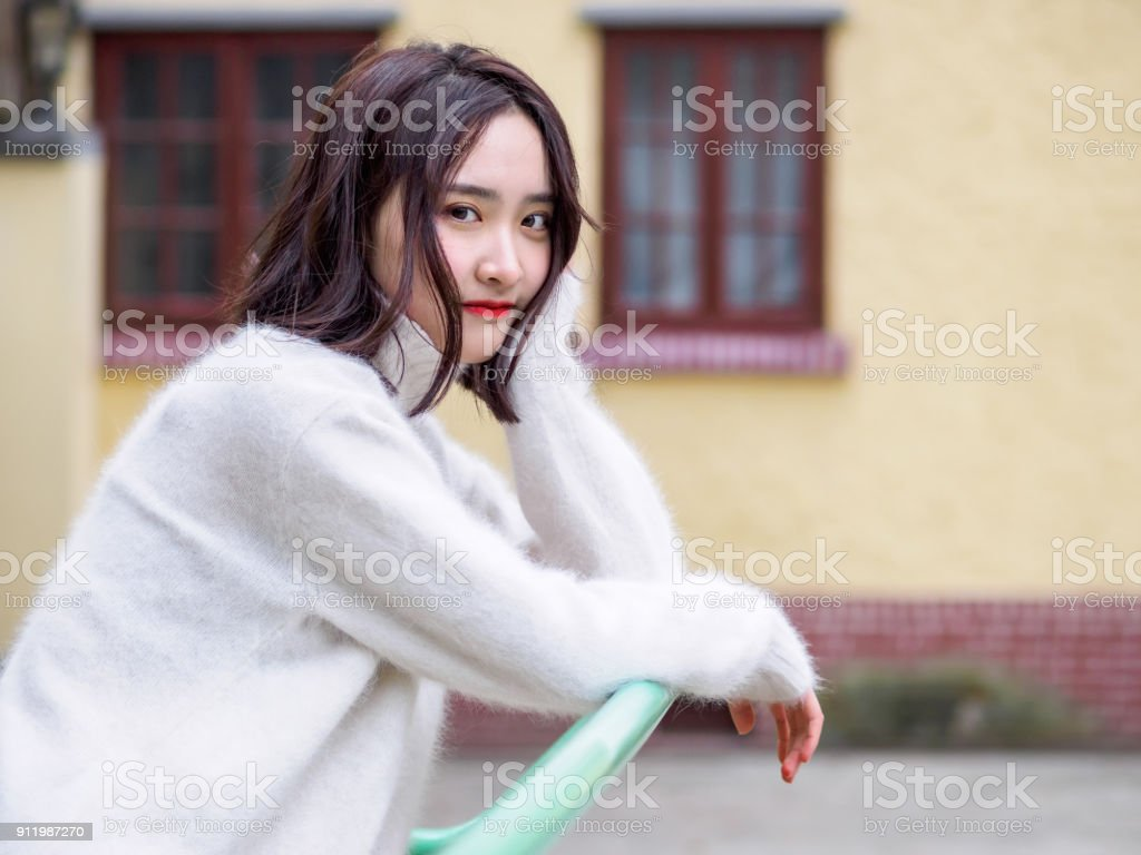 Beautiful young brunette woman looking at camera with blur house background. Outdoor fashion portrait of glamour young Chinese cheerful stylish lady, emotions, people, beauty and lifestyle concept. stock photo